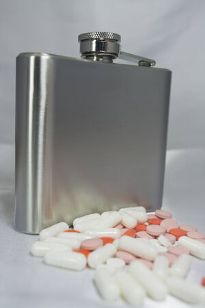 Silver metal flask with pills on a grey . photo