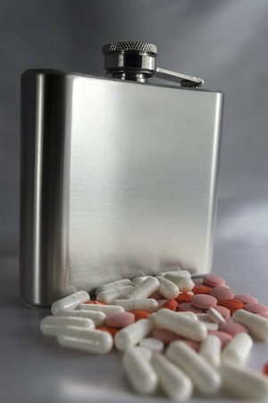 Silver metal flask with pills on a grey wall photo