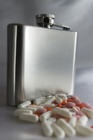 Silver metal flask with pills on a grey  photo