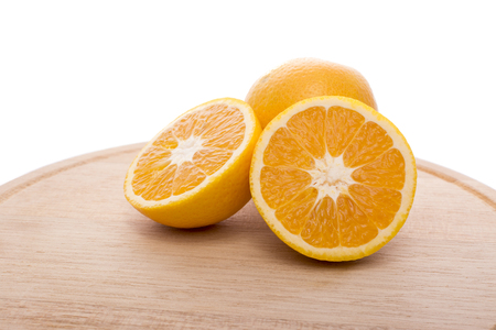 Approach and presentation of an orange split in half and a full in the back. They are on a wooden plate and white background Standard-Bild