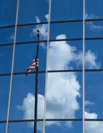 Flagmire - the observed reflection in a glass building of an American Flag twisted around its own flagpole in an attempt to display its colors, venetian blinds visible inside the building