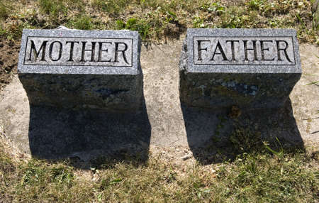 grave site: Mother and Father gravestones casting a shadow in the afternoon sun