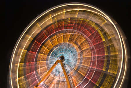 wheel spin: Ferris wheel at night, spinning circular colors of red, orange, yellow and blue