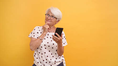 Senior woman holding smartphone and thinking about new post for social media. High quality photo