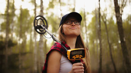 Portrait of young caucasian woman in the forest holding metal detector and smiling. High quality photo