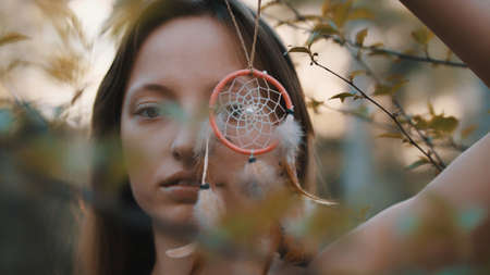 Young beautiful and mysterious woman spinning dreamcatcher in the forest. High quality photo Foto de archivo