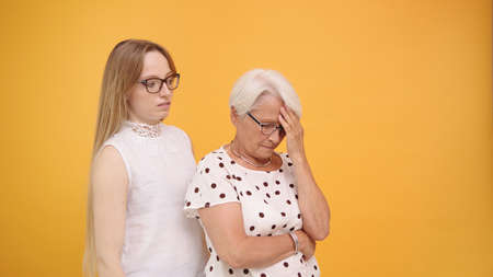 Young woman calming down senior lady after bad news. Family love and care concept. High quality photo Imagens
