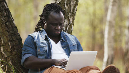 New normal. Remote work concept. African man using laptop in the nature. High quality photo Stock Photo