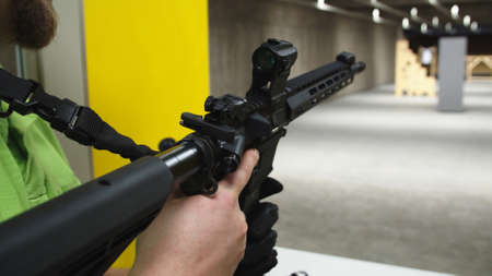 Adult loading an assault rifle at a shooting range