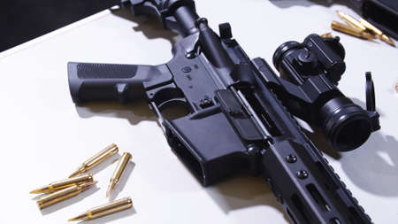 Tactical rifle with a colimator sight and some ammunition on the table.