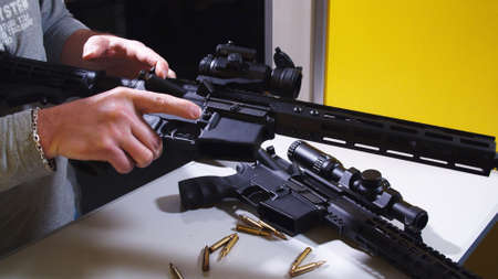 Shooting instructor loading an assault rifle at a shooting range. High quality photo