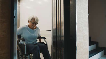 elderly disabled woman using the lift in the wheelchair. High quality photo