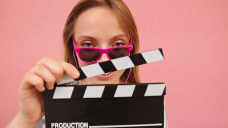Young caucasian woman with pink sunglasses holding a classic black filmmaking clapperboard. High quality photo