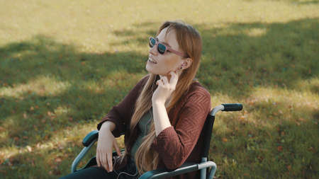Disabled young caucasian woman listening the music in the park in the wheelchair. High quality photo Stock fotó