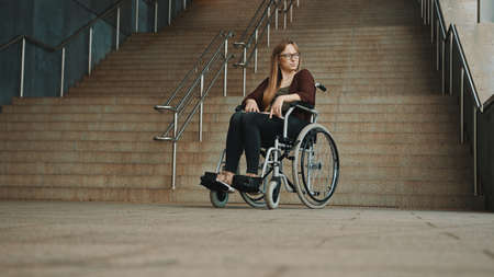 Hopeless young woman in the wheelchair in front of the inaccessible stairs. High quality photo