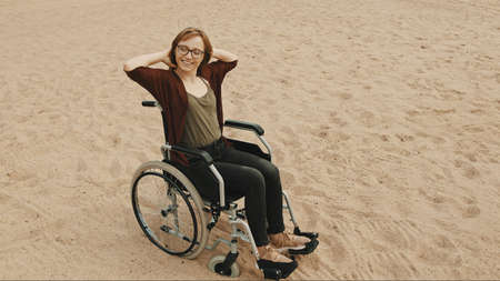 Young disabled woman on the sandy beach sitting in the wheelchair. High quality photo