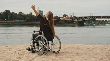Happy young disabled woman in the wheelchair enjoying the vacation on the sandy river coast. High quality photo