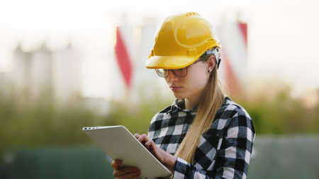 Young woman engineer with a yellow hard hat and working on the tablet. High quality photo