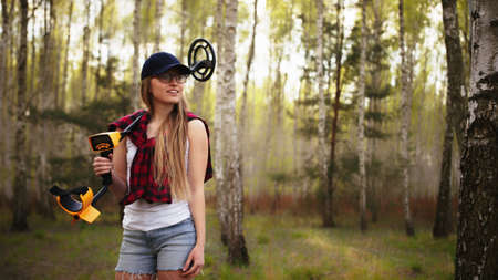 A young woman with a smile holding a metal detector over her shoulder in the forest. High quality photo Standard-Bild