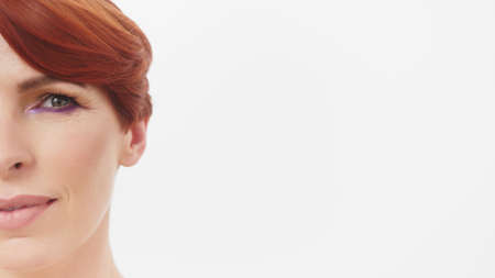 Beauty half face shot. Beautiful middle aged caucasian redhead woman with wrinkles around the eyes isolated on white. High quality photo Banque d'images