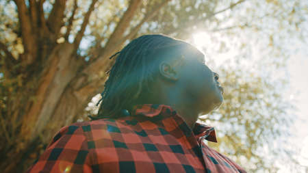 African man takes a big breath rises hands and look up a the sky. Sun rays comming through the tree. Hope and prayer concept. High quality photo