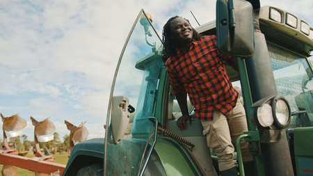 Young african farmer going out of the green tractor on the farm. High quality photo