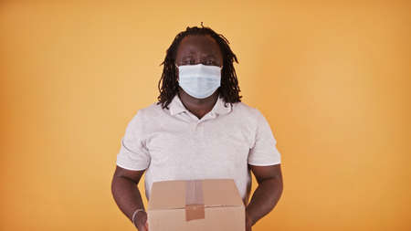 African delivery man with face mask - courier handing the package box - copy space isolated. High quality 4k footage Фото со стока