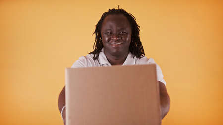 Delivery concept: African delivery man - courier handing the package box - copy space isolated. High quality 4k footage