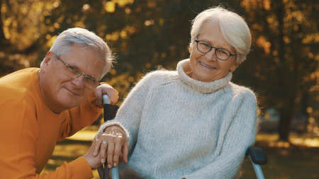 Old couple having romantic autumn day in forest. Hugging tree and smiling. High quality photo