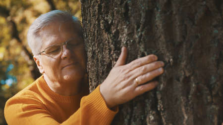 An older man lovingly hugging and leaning face to tree trunk feels relaxed and good on the autumn day. High quality photo