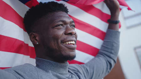 Black man african-american with USA flag on the balcony. 免版税图像