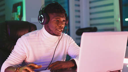 Happy young black man with illuminated headset using laptop. Home office and remote work concept. Stock trader portrait. High quality photo