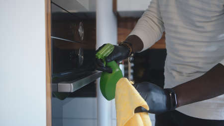 Close up, black man with gloves spraying and cleaning built in owen. High quality photo