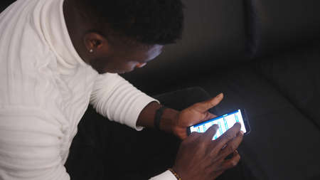 Young black man browsing stock app on smartphone. High quality photo