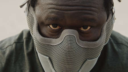 Close up, african man with mask over his face and red eyes. Scary warrior. High quality photo