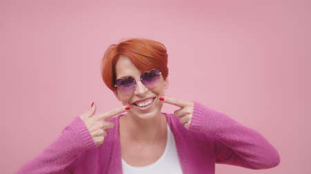 Attractive middle aged woman with red hair pointing fingers on her white teeth. High quality photo