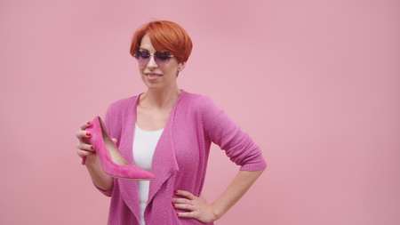 Mature woman with red short hair holding high heal shoes Isolated on purple background. High quality photo Фото со стока