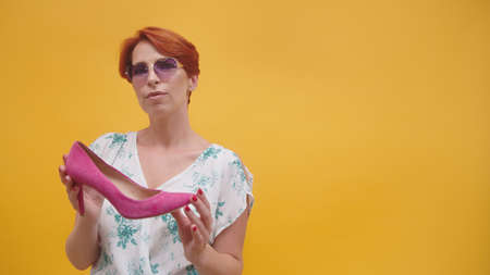 Mature woman with red short hair holding pink purple high heal shoes Isolated on orange background. High quality photo Фото со стока