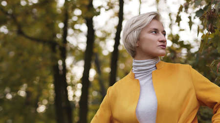 Portrait of annoyed blond woman in the park waiting for someone and looking around. High quality photo