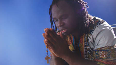 african black man in traditional dress praying with rosary. High quality photo
