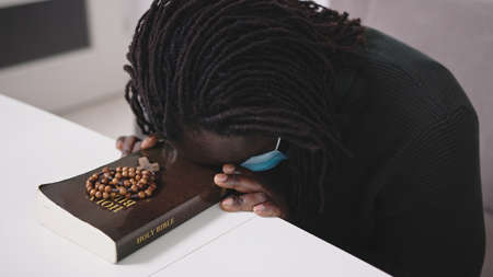 Black African Descent Man With Face Mask Praying on Holy Bible Book and Rosary. Seeking Hope in Religion During Covid-19 Virus Pandemic Outbreak. High quality photo