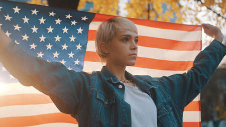 Portrait shot of young blond woman holding usa flag in the park. Election and rights of voting concept. High quality photo