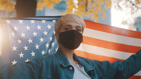 USA presidential election concept. Proud woman with face mask proudly holding american flag outdoors. High quality photo