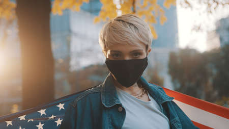 USA presidential election concept. Confident young woman with face mask proudly holding american flag outdoors. High quality photo