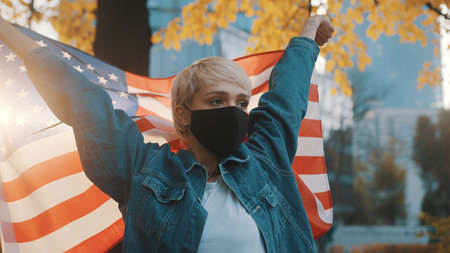 Young woman with face mask proudly holding american flag outdoors.USA presidential election concept. . High quality photo
