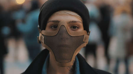 Portrait of young woman with face mask in the crowd. High quality photo