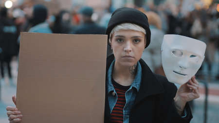 Young woman removing Theater mask while holding black cardboard in the crowd. Protest against discrimination. High quality photo