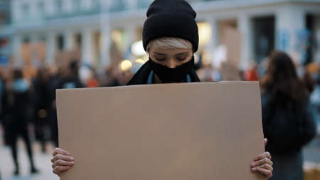 Protest and demonstrations. rebellious woman with face mask striking . High quality photo