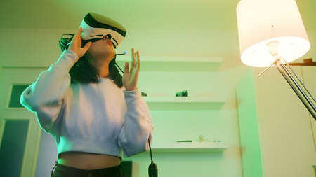 Young woman with VR headset experiencing Virtual world for first time. High quality photo