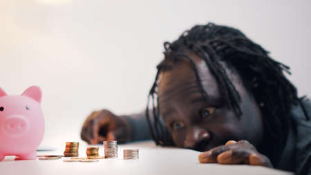 Desperate black man looking sad in the coins near the piggybank. High quality photo